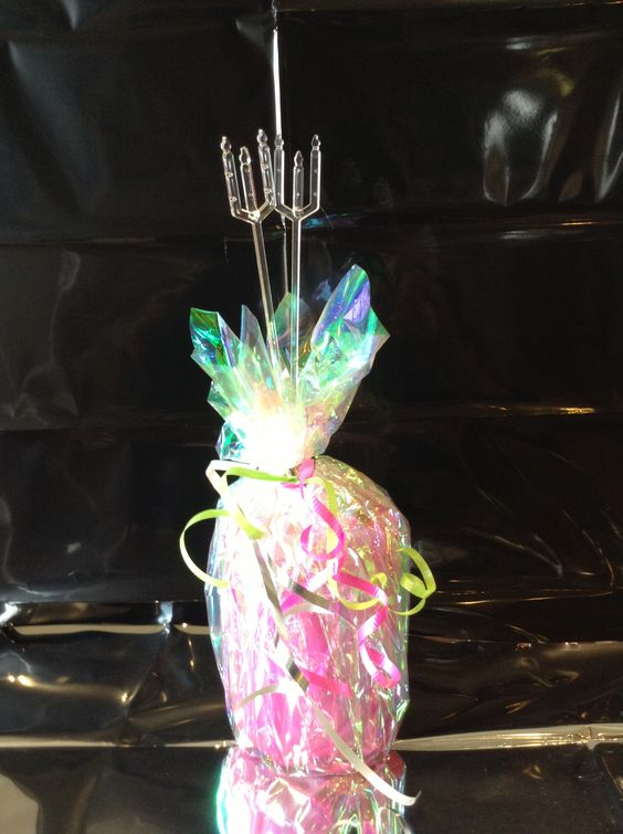 Graduation centerpieces!  Made with soup can filled with gravel, wrapped in pink treat bag and iridescent cellophane and pink and lime green curling ribbon; stick in photo spikes for displaying pictures.  Adds a touch of color!