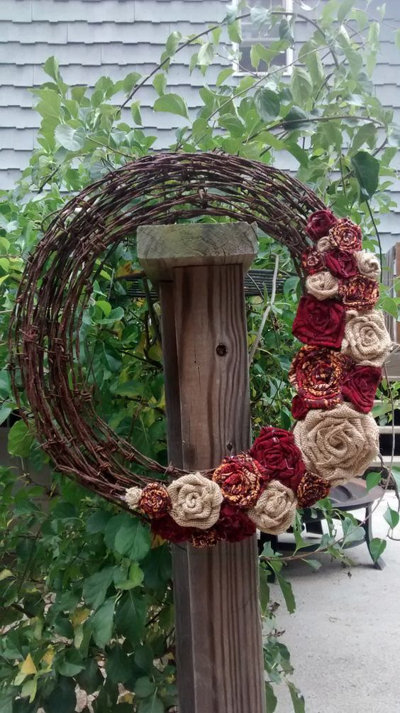 This wreath is a great addition for your fall decor. The rusty barbed wire wreath features brown burlap and fall colored cloth flowers. The