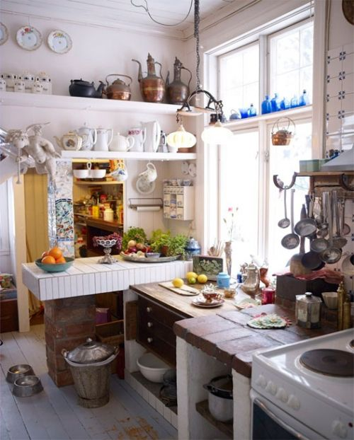 Fun, cozy space in which to cook. Love the water urns high on the shelf and the cluster of ladles by the stove.