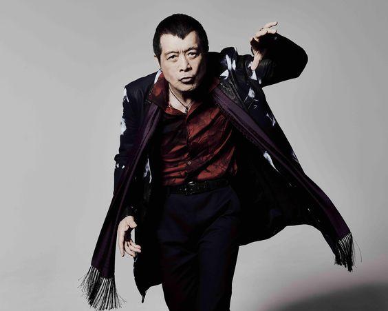 赤いシャツに黒いスーツを着て立っている矢沢永吉の画像