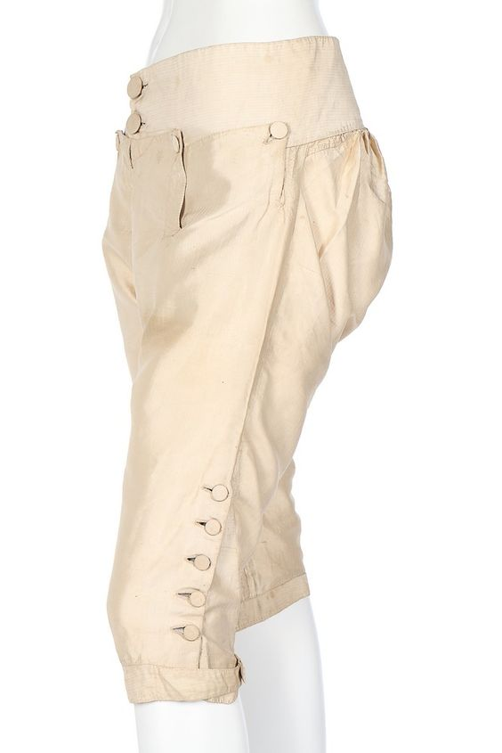 Pair of breeches, 1770s-1780s. Ivory silk taffeta, with self-stripe and small fall, fabric covered buttons.