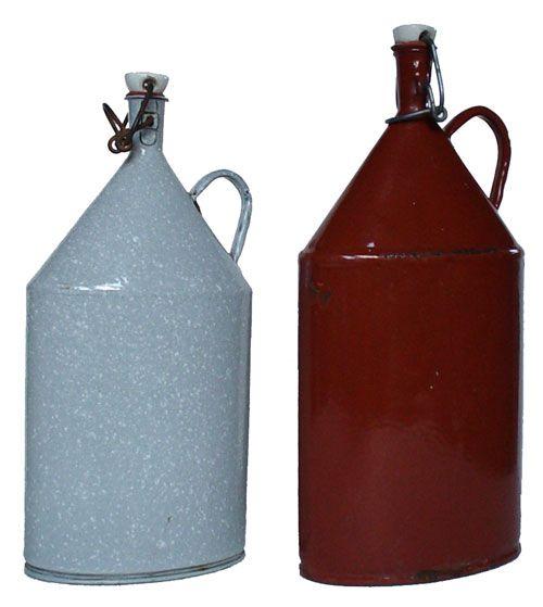 Sammlungsstück: Zwei Kaffeeflaschen -  Eisenblech mit Emailüberzug, Porzellan, Gummi, 13,5 x 27 x 8 cm und 14,5 x 30 x 8 cm, um 1930. In den Jahren der industriellen Revolution gab es keine Firmen-Kantinen. Die Arbeiter mussten Essen und Getränke selbst mitbringen. Für die Frühstückspause waren die in Tageszeitungen eingewickelten Butterbrote und die mit einem Bügelverschluß versehenen Kaffeeflaschen gedacht. Beide Flaschen besitzen eine ovale Grundform, über die sich das schmale Gefäß…