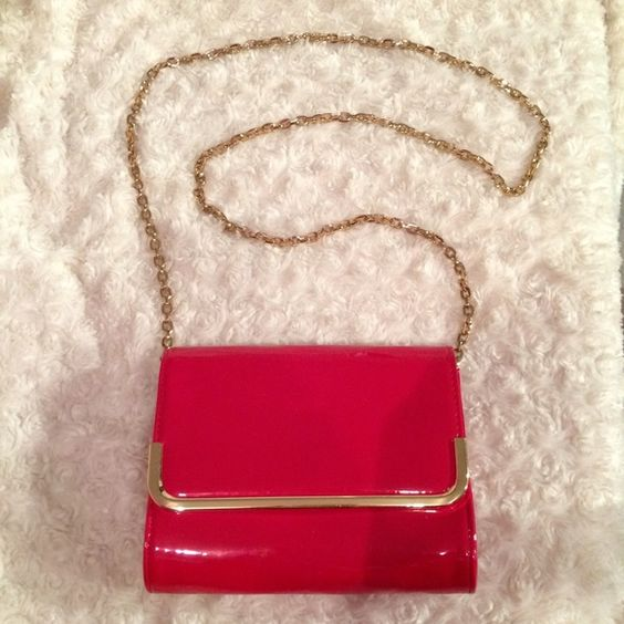 Red patent clutch purse Red patent purse with gold chain. You can tuck the chain in to turn it into a clutch. Cute compact purse but spacious to fit all your money, phone, keys, makeup and small accessories. Bags Clutches & Wristlets