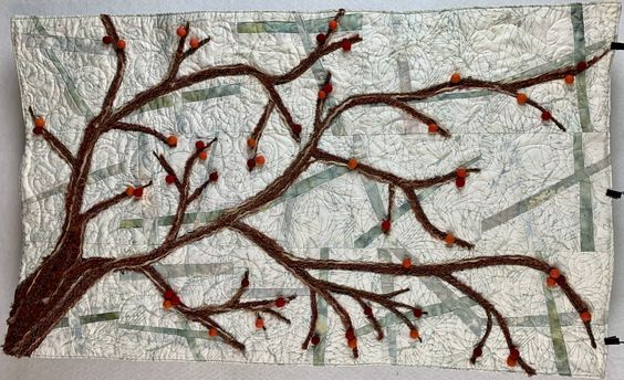 I pieced the quilt and quilted it all then I painted branches and a trunk with  fabric paint.  Couched down 5 different brown yarns over the paint.  Then glued on wool felted balls of different colors that I bought online.