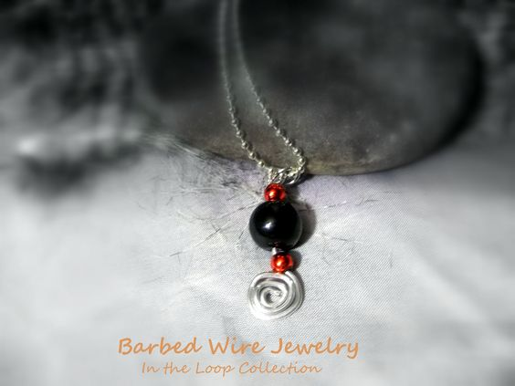 """A handmade one of a kind wire wrapped ancient swirl design necklace featuring a large black bead and 2 small red beads on an 18 inch silver ball chain. From the """"In The Loop Collection"""". The swirl design is made from aluminum wire.      https://www.etsy.com/listing/185644151/necklace-with-an-ancient-wire-wrapped?ref=listing-shop-header-3"""