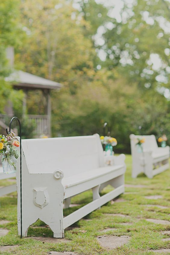 white church pews with colorful florals in aisle at outdoor wedding ceremony | Simply Charming Socials | Atlanta Wedding Planner