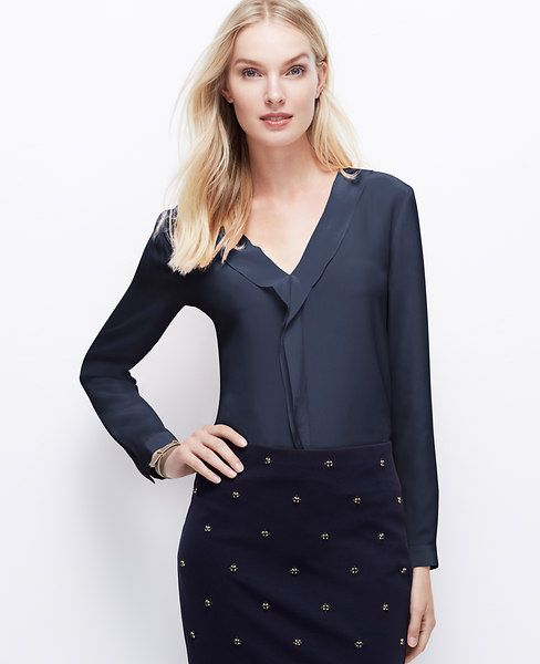 A cascading ruffle imparts utter femininity to this luxe silk style. V-neck. Long sleeves with button closure. Shirttail hem.