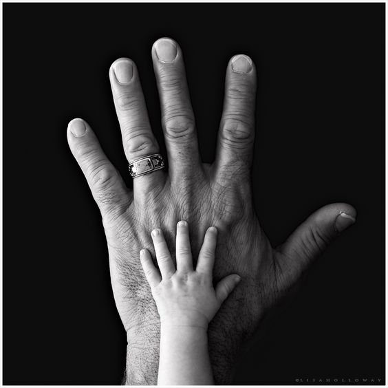 Size - the contrast between the small and large hand creates a focal point in the center of the picture.