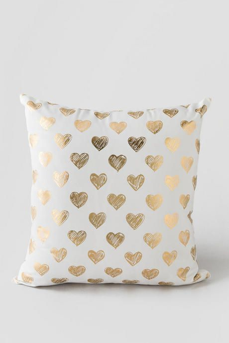 Gold Hearts Pillow. Shiny gold hearts are printed on the front of the pillow for a bold yet feminine touch.