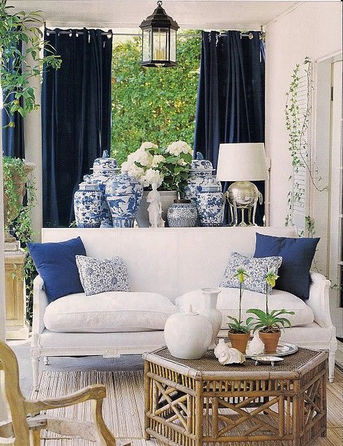 Living room: Blue curtains, white couch and walls, multitude of blue and white patterned vases, wooden table and blue cushions: