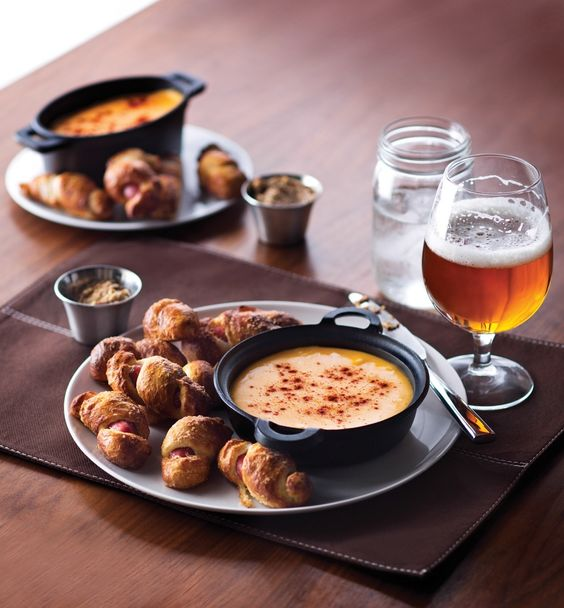Yankee Franks: pretzel-wrapped smoked sausages with cheddar cheese sauce. Your favorite comfort foods will be available at American Icon Grill on Quantum of the Seas. #thischangeseverything