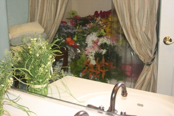 """This is a bathroom and you're looking into a mirror which is reflecting a huge pile of silk flowers.  Let's say, at times it was difficult to own a wedding gown business, especially if time to go on the road.  Every room was filled with """"something."""""""