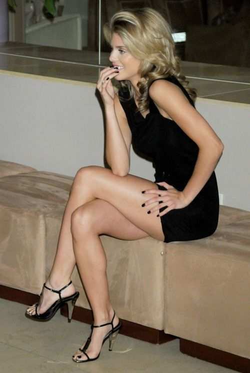 a blonde with black dress, black heels and black nails