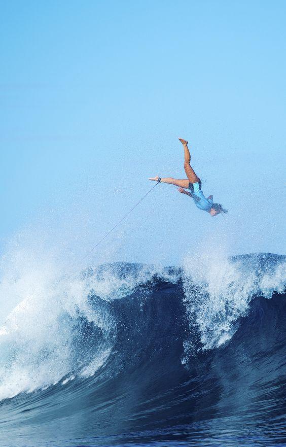 波の上を飛ぶ女性サーファー