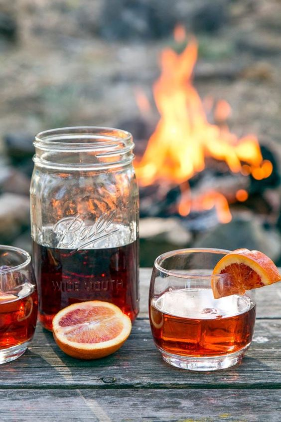 Camping Cocktail Hack 101: Make your cocktails ahead of time! By making a big batch of Negronis at home, you can keep the cocktails flowing around the campfire all night long.