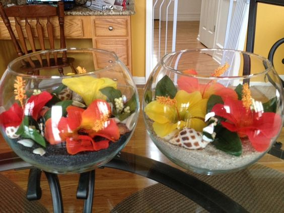 I made these for a Hawaiian themed dinner in celebration of our upcoming company trip to Hawaii. Some had white sand, some had black sand. Glass globe vases with 2 bags of sand, shells, Hawaiian flowers and greenery picked off of a Hawaiian flower garland, small tea light glass globe, and battery operated flickering tea lights.