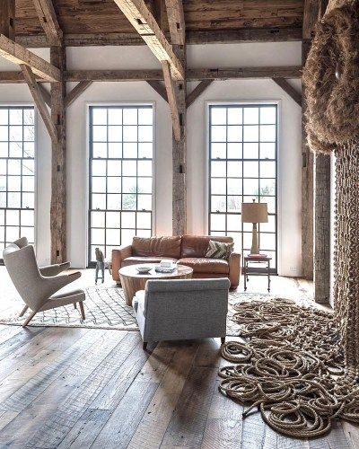 Modern Rustic Farmhouse with steel windows, rustic wood beams, modern furniture, and retro art. Design by Jennifer Bunsa. #modernfarmhouse #livingroom #rusticdecor