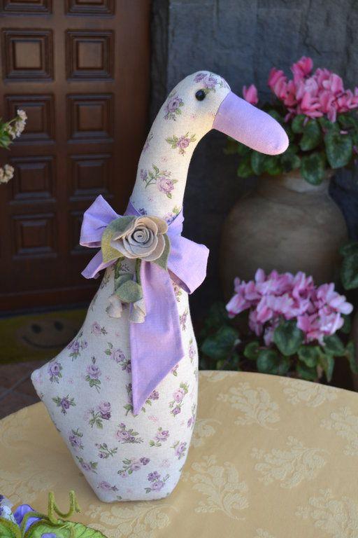 PAPERA FERMAPORTA LUISELLA - Mod. 01 - PatriziaB.com  Realizzata artigianalmente in delizioso tessuto di cotone, la papera Luisella è abbellita da morbido fiocco di lino con fiori di pannolenci