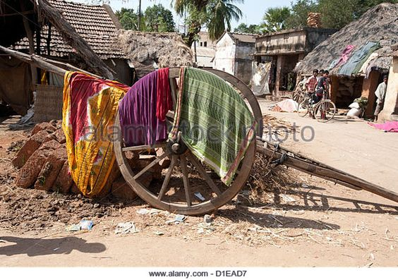 Washing drying over wooden cart wheel of wooden handcart in the street, Naupatana weaving village, rural Orissa, - Stock Image