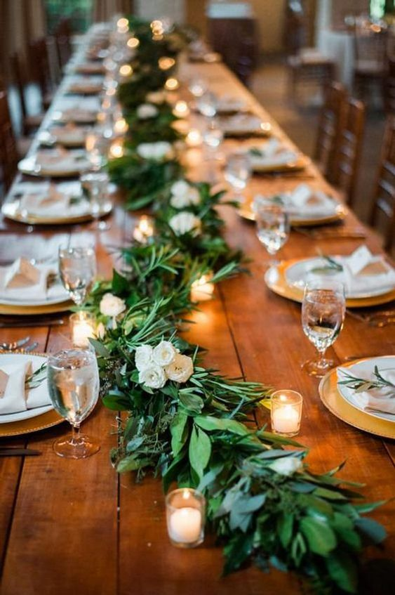 An Uncovered Table With A Long Greenery And White Bloom Garland Plus Candles That Cr Wedding Reception Table Decorations Wedding Reception Tables Wedding Table