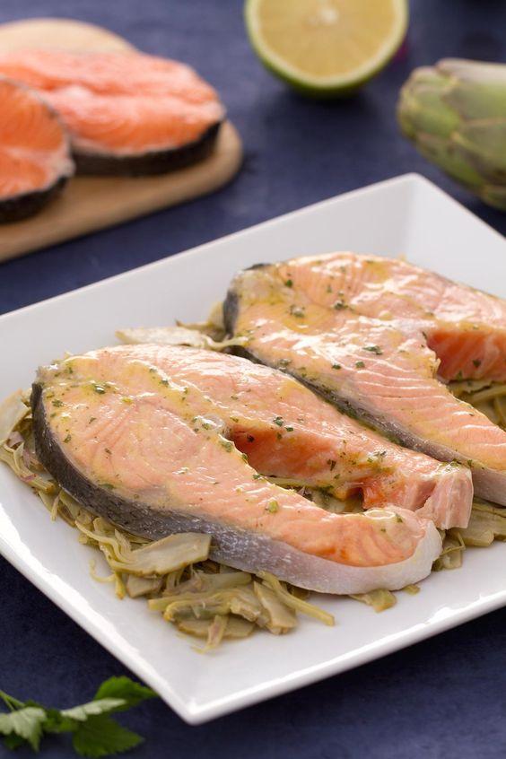 Salmone alla limoncina: tranci di salmone norvegese cotti al forno con un'emulsione di olio, limone e prezzemolo e serviti su un letto di carciofi saltati in padella. #Giallozafferano #ricetta #recipe #salmonenorvegese