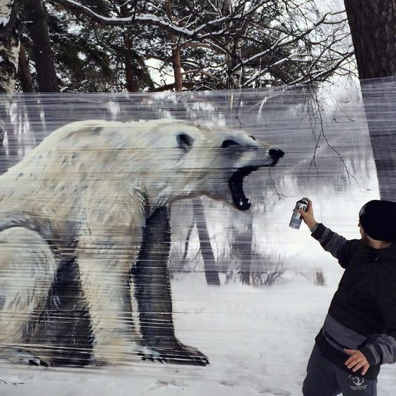 Artist painting giant animals in cellophane in the woods