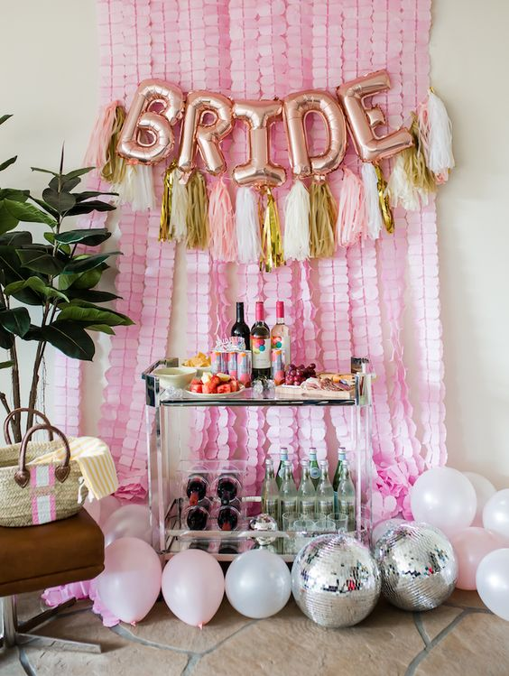 Wedding Wednesday: 5 Essentials You Need For The Perfect Bachelorette Party · Haute Off The Rack, Bachelorette Set Up, How to Decorate for your bachelorette party, Bride Balloons, Tassel Garland, Disco Balls, Bar Cart, Streamers, Barrington Beach Bag