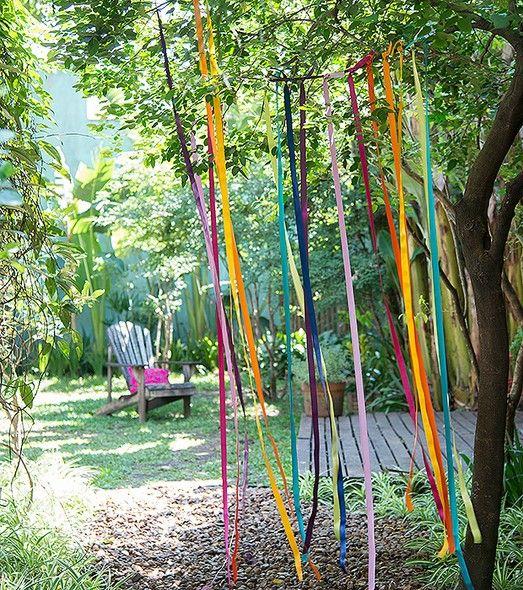 Decoração para festa no jardim  Fitas coloridas presas no galho da