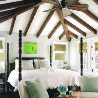 Pale blue walls, vaulted ceiling, island style fan, black poster bed, bamboo window covering.