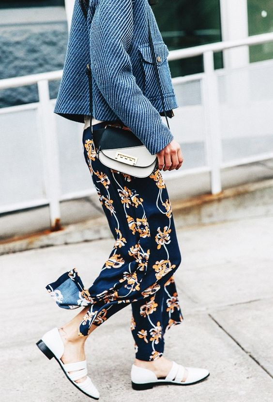 A blue jacket is worn with a two-toned shoulder bag, printed trousers, and white pointed toe shoes