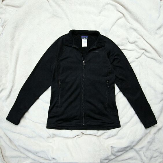 "Patagonia Women's R1 Full Zip Fleece Jacket Excellent condition! This is an awesome black R1 regulator full-zip fleece jacket by Patagonia! It is a great jacket to use as a mid-layer or a light-weight jacket on warmer days. It has two zippered waist pockets and two drop-in pockets on the inside. It was made in Columbia with 93% polyester, 7% spandex. It measures 27"" long, 20"" across the chest from under the arm, and has a 22.5"" arm inseam. The fabric tag is a little faded from washing, but…"