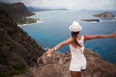 Rapariga que aprecia a vista sobre o vale de cima de um estoque de montanha foto