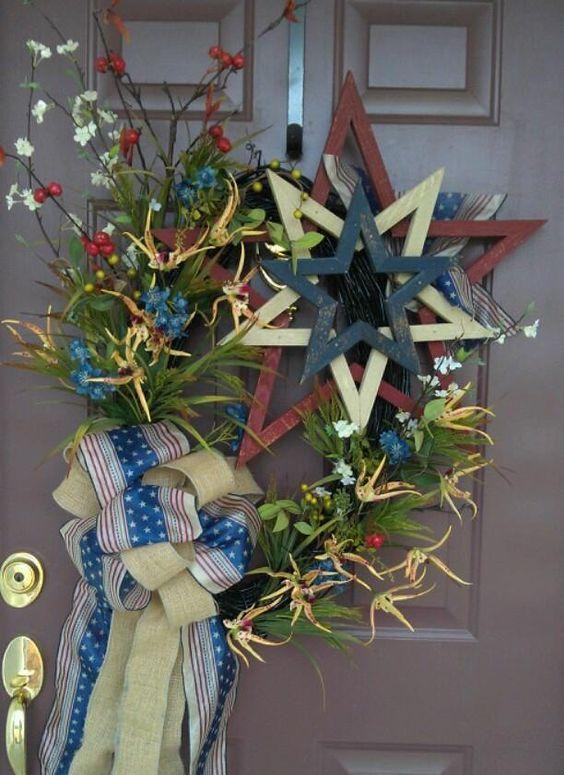 Patriotic wreath with red, white and blue. A large wooden star, star-shaped yellow orchid, red, white and blue flowers, various grasses and greenery with patriotic ribbons.