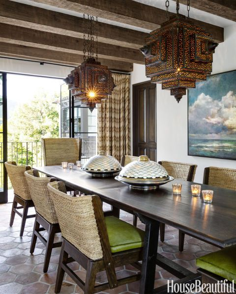 Lacy brass lanterns from Morocco glow above a dining table from Lucca Antiques. Mimi London chairs have seat cushions in a Kyle Bunting hide. The plaster walls throughout the house are color-matched to Benjamin Moore's Swiss Coffee.  Curtains in Hill Brown's Zigoto.
