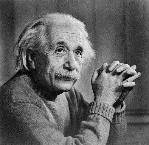 肘をついて手を組んでいるアルベルト・アインシュタインの壁紙・画像
