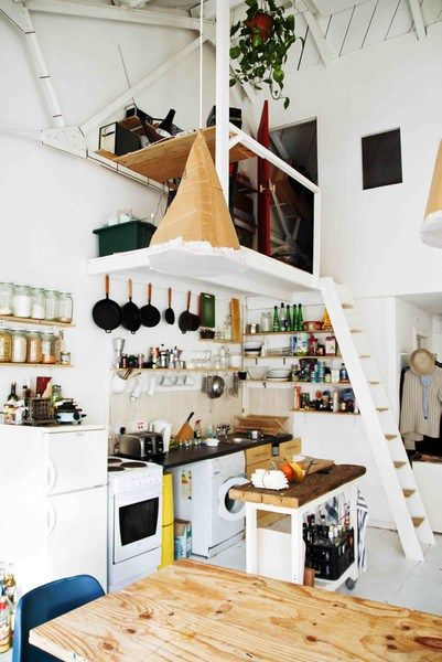 Collections of things, when displayed, turns clutter into style, viz. the dry goods jar, matching hanging pots, green bottles on the shelves.