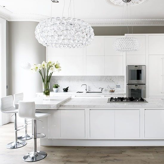 Dramatise a white kitchen with opulent accessories, such as this crystal pendant light, for a look that oozes personality. Flooring will give a scheme depth and natural-look timber and stone (whether it's real, laminate or replica vinyls or ceramics) creates a warming counterpoint to shiny white cabinets
