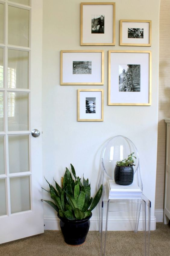 Gallery wall with Target frames painted gold with black and white photos.: