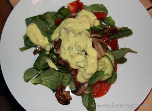 Angebratene Zwiebeln und Champignons auf knackigem Gemüse und Feldsalat mit einem selbst gemachten Sojajoghurt-Senf-Dressing mit Kräutern.