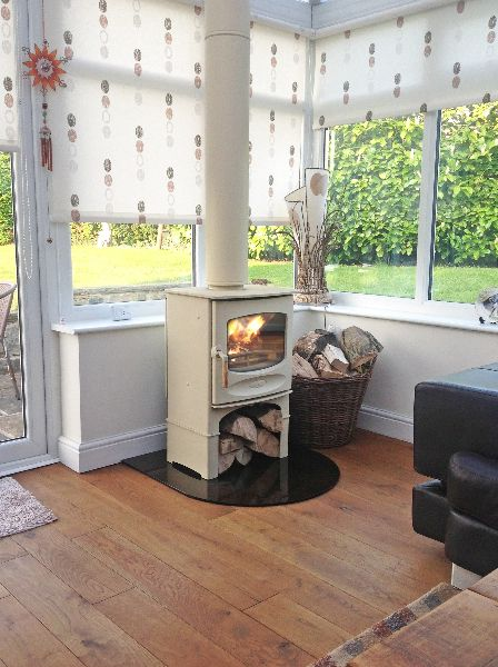 Charnwood C-FIVE in almond on log store on bronze tinted glass hearth connected to a twin wall insulated flue and situated in a conservatory.