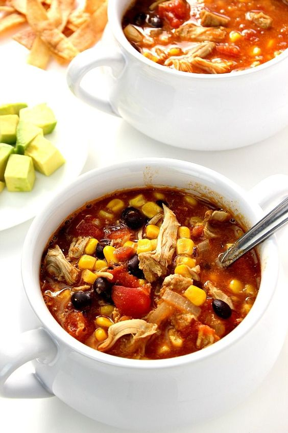20-Minute Chicken Enchilada Soup Recipe - quick, easy and filling soup packed with beans, chicken, tomatoes and corn! Top it with tortilla chips, cheese, sour cream and avocado!