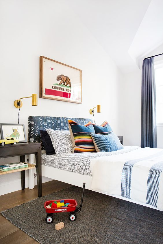 A Californian boy's room with pillows made from Mexican blankets and gold wall sconces