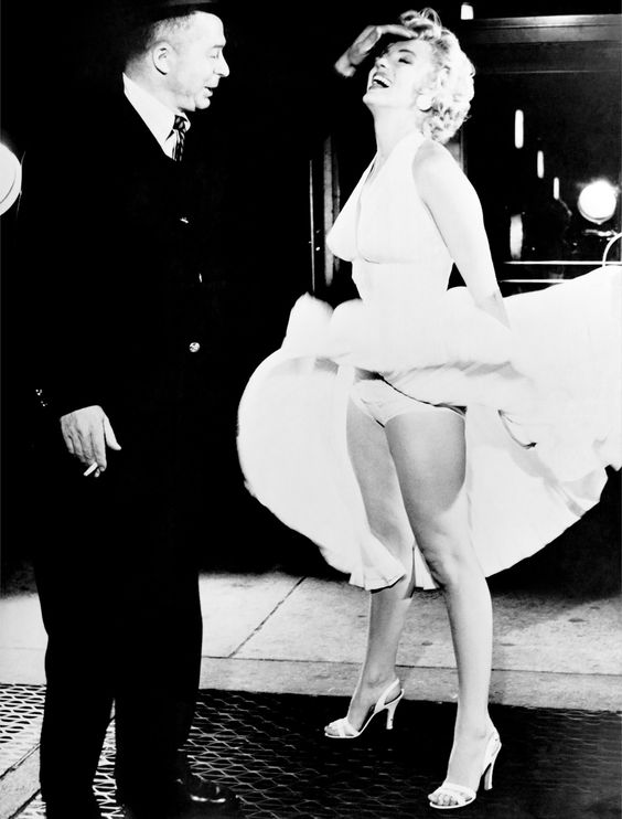 Marilyn Monroe stand over an air vent which causes her dress to fly up as director Billy Wilder 1955