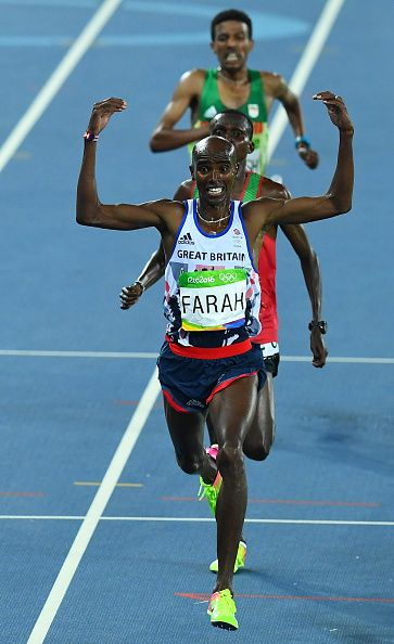 Britain's Mo Farah celebrates as he crosses the finish line to win the Men's…
