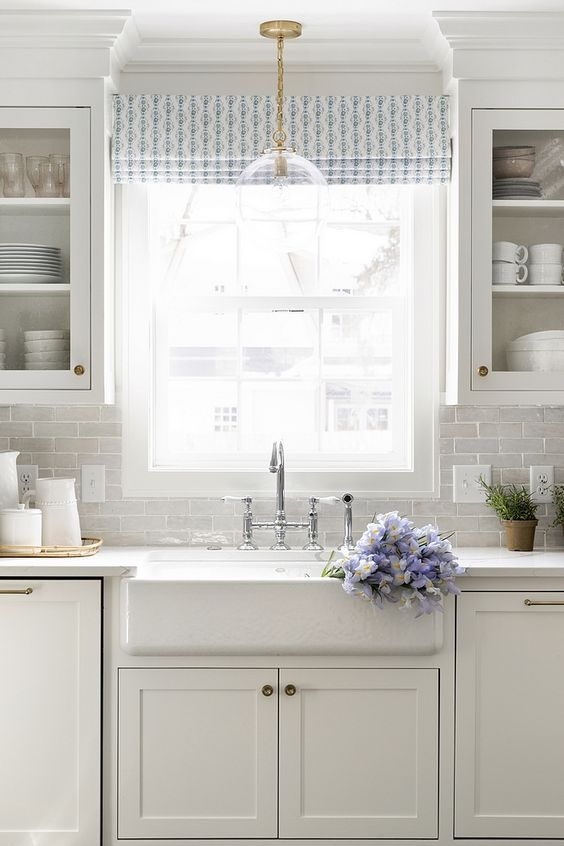 Soft white kitchen with white terracotta subway tile backsplash white quartz countertop and white farmhouse sink. Come see 36 Best Beautiful Blue and White Kitchens to Love! #blueandwhite #bluekitchen #kitchendesign #kitchendecor #decorinspiration #beautifulkitchen