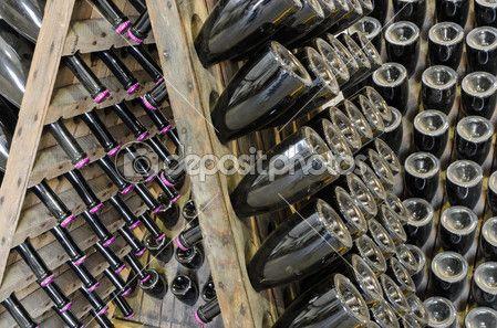 garrafas empoeiradas com espumante brut na cremalheira de madeira no cofre da adega