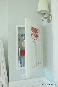 Stay at Home-ista: Bathroom medicine cabinet behind art instead of a mirror