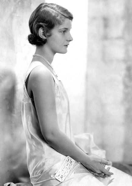 Actress Helen Chandler in moire taffeta with a diamond-encrusted brooch at her hip. Brooches were a popular accessory to accentuate drop waists or swags at the front or sides of the hips, 1927