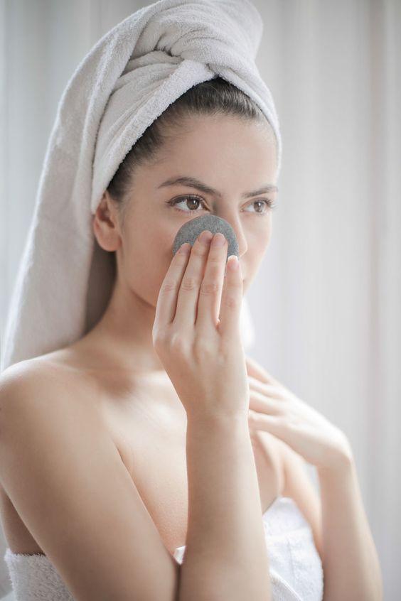 chica limpiándose el rostro con un disco de algodón