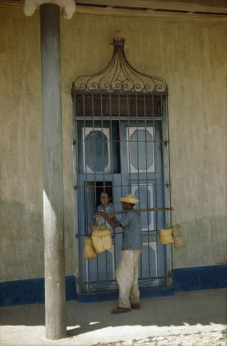 1940's Housewife buys from traveling vendor at her door.Trinidad, Cuba.//MELVILLE B. GROSVENOR/National Geographic Creative